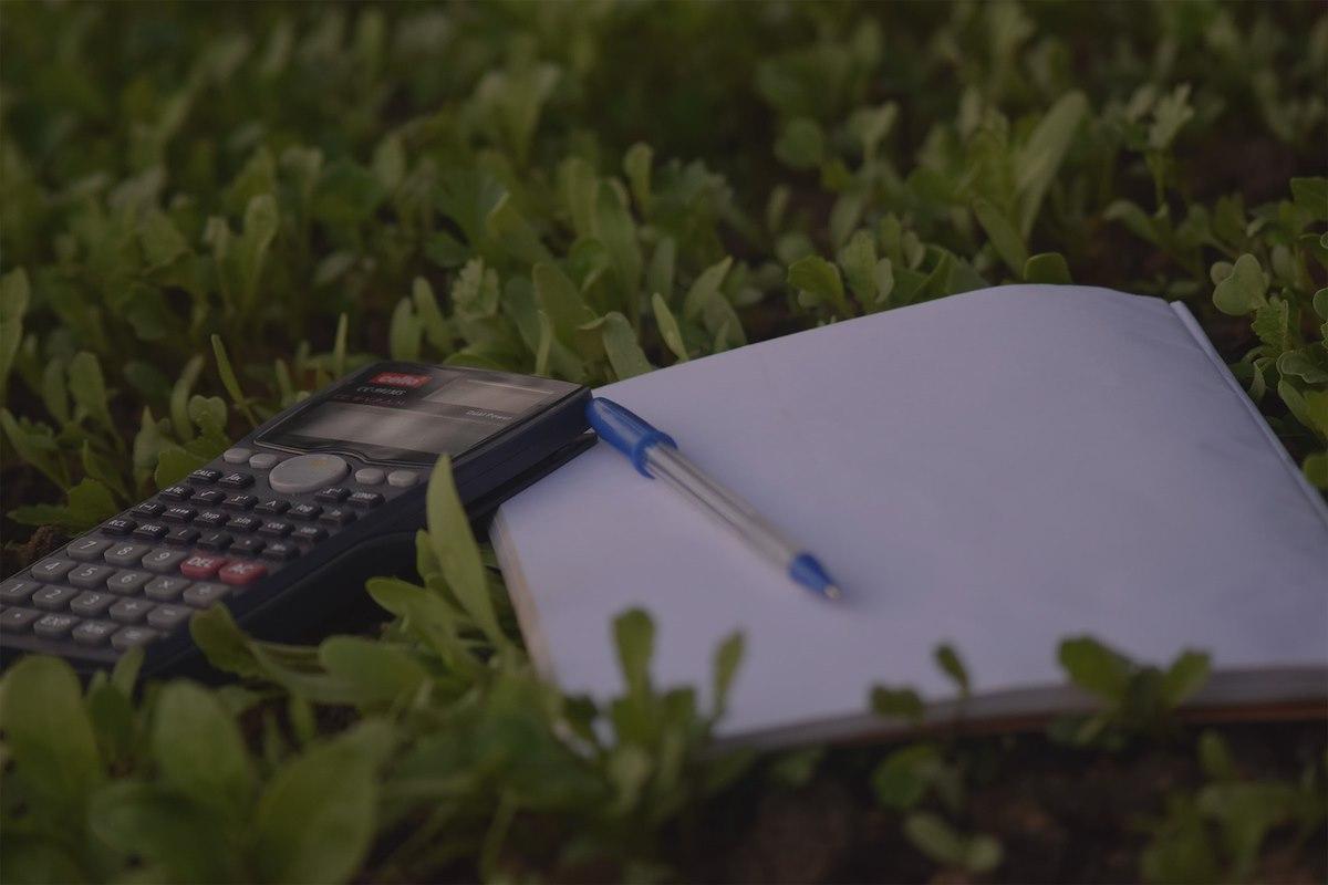 caderno e calculadora pousada na relva