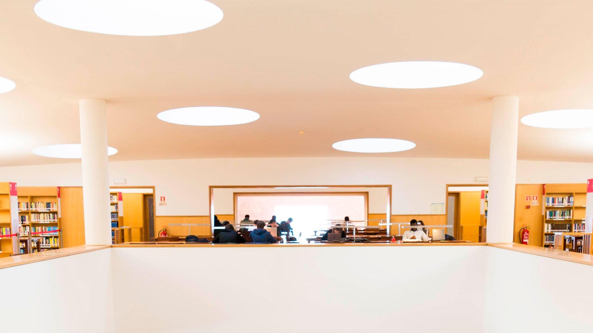 Jovens a estudar na biblioteca. Luzes no teto. Duas colunas na horizontal entre os estudantes. Secretárias.